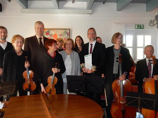 das geehrte Ensemble mit Martin Hageböke (hält die Urkunden in der Hand), der Preisverleiherin Monika Manke (in grau) und hinten (groß mit Krawatte) Bürgermeister Stefan Bauer