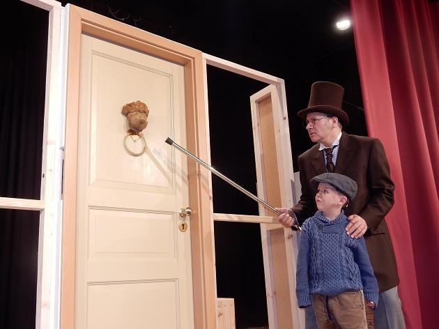 der Geizhals Ebenezer Scrooge (Chrischan Dauer)kommt mit dem kleinen Sternsinger (Lasse Calm) zu einer Tür mit einem sprechenden Türklopfer