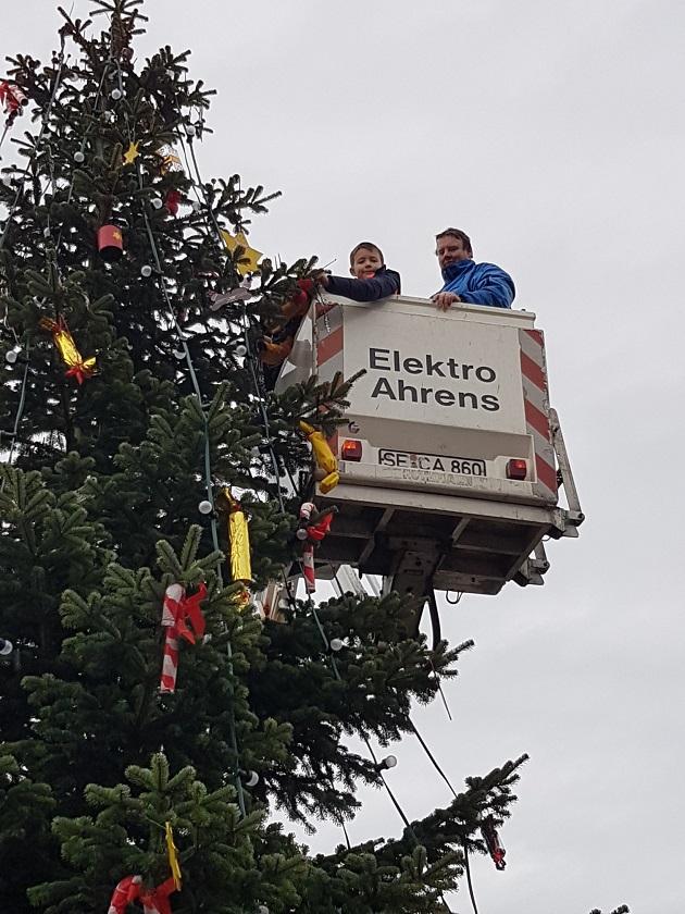 Die Mitarbeiter der Firma Elektro Ahrens brachten die Lichterkette mit einem Hubsteiger an und nahmen währenddessen die Schulkinder mit in die Höhe
